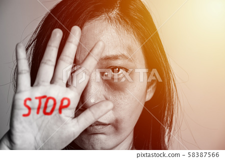 stop violence against women campaign. Asia woman with bruise on arms and face raised her hand for dissuade, hand write the word STOP in red color. 58387566