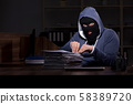 Male thief in balaclava in the office night time 58389720