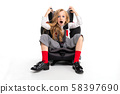 A shocked little girl with makeup and long blonde hair in a white shirt, red pull-ups, pants in a 58397690