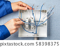 Handyman installs circuit breakers for home wiring 58398375