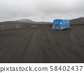 blue metal garbage container standing alone in black lava sand desert in Iceland, hills and gray sky 58402437