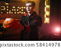 A young man in a Halloween costume of Count Dracula holds a carved pumpkin 58414978