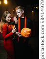 Guy in a Halloween priest costume holding a carved pumpkin in his hand. 58414979