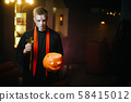 Guy as a priest holds a cross and a Halloween pumpkin 58415012