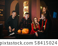 Portrait of friends in Halloween costumes sitting looking at the camera 58415024