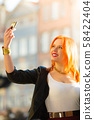 woman taking self picture with smartphone camera 58422404