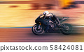 motorcycle racer rides on a sports track 58424081