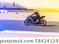 motorcycle racer rides on a sports track 58424129