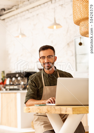 Entrepreneur owning coffee shop sitting at the table 58426379