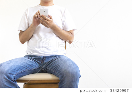 Man sitting on a chair and operating a smartphone 58429997