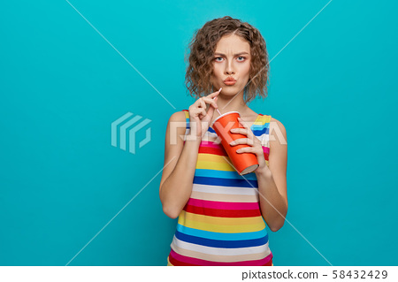 Serious girl with curly short hair drinking cold water 58432429