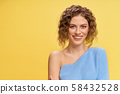 Girl looking at camera and laughing on yellow background 58432528