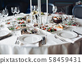 Served table with snacks and empty wine glasses. 58459431