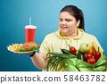 Oversized girl choosing between healthy eating and fast food 58463782