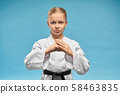 Karate girl with black belt practicing hands position. 58463835