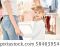 Cute little girl in boutique holding hands with mom, posing. 58463954