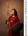 Female spartan warrior with shield and spear and chewing gum 58464582