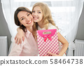 Cheerful mother and daughter hugging posing with present 58464738