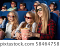 Mother and daughter in 3d glasses eating popcorn in cinema 58464758