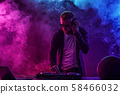 Trendy male dj posing against mixing console 58466032