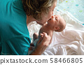 Rocking the baby in her arms at home 58466805