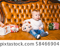 Happy little smiling boy with christmas gift box. Beautiful little baby, sits on asofa with gift 58466904