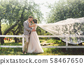 Caucasian couple in love bride and groom standing in embrace near wooden white, rural fence in park 58467650