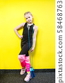 Theme sport and health. Beautiful caucasian child girl with pigtails posing yellow background with 58468763