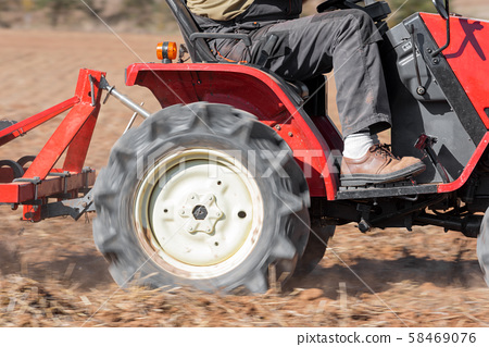 Red Tractor With Plough Plowing Field Soil Close Up View. 58469076