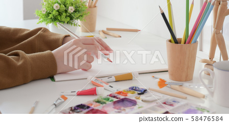 Close-up view of young female artist painting her 58476584