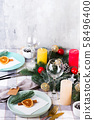Festive Christmas and New Year table setting with dry orange and cinnamon on a gray textile. Dining 58496400
