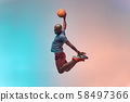 Slam dunk. Full length of young african backetball player jumping against colorful background 58497366