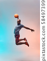 Basketball player in action. Full length of young african sportsman playing basketball and jumping 58497399