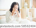 Unwell asian senior woman blowing nose in bed,Senior woman covering nose with tissue paper in bed. 58502404