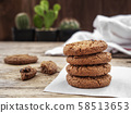 stack of chocolate chip cookies on white napkin paper on wooden table decorate with cactus at background 58513653