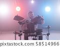 People, music and hobby concept - man plays with drumsticks on drums on the stage 58514966