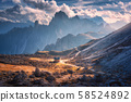 Small house in beautiful mountain valley, orange grass, stones, blue sky with clouds at sunset  58524892
