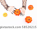 Halloween composition with witch hands holding a 58526215