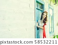 beautiful young woman wearing national ukrainian clothes sitting in wooden hut 58532211
