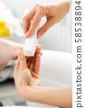 Woman podiatrist polishing nail of man during pedicure 58538894