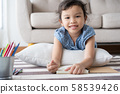Asian  little  girl is drawing  and smile while  on the carpet in the living room at her home 58539426
