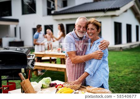Senior couple with family outdoors on garden barbecue, grilling. 58540677