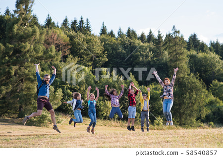 Group of school children with teacher on field trip in nature, jumping. 58540857