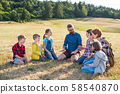 Group of school children with teacher on field trip in nature, talking. 58540870