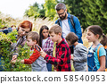 Group of school children with teacher on field trip in nature, learning science. 58540953
