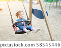 Little Caucasian girl riding swing at playground 58545446