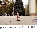 Toddler girl in rain boots playing with birds on city square. Outdoors childhood activity 58546073