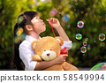 Asian girl play a bubble from soap in out door 58549994