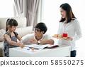 Asian family do homework togather in living room 58550275