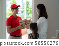 Asian woman recieve pizza box from pizza boy at 58550279